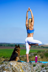 beautiful blonde girl practices yoga with dogs, german shepherd