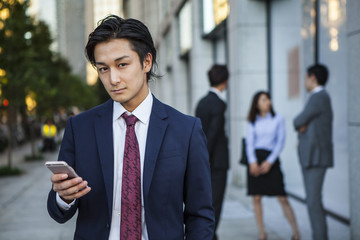 Businessman, looking at a smart phone in the office district