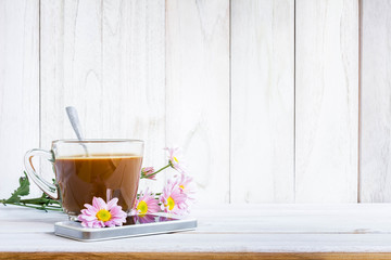 Coffee cup and a mobile phone with flowers on the white wooden