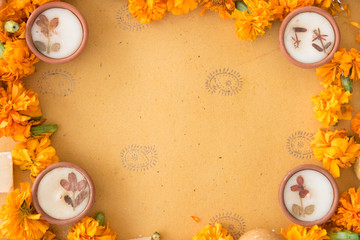 Diwali prayer celebration preparation with sweets and diyas and marigold flowers on handmade paper with Indian motifs