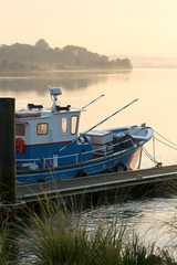 Fishing boat on a river at sunrise