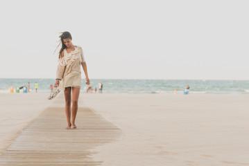 Barefoot pretty woman walking along beach
