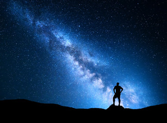 Milky Way. Colorful night sky with stars and silhouette of a standing man on the stone. Blue milky way with man on the mountain. High Rocks. Background with galaxy and silhouette of a man. Universe