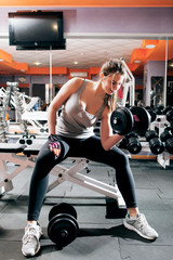 Young smiling woman training with dumbbell at professional gym. Athlete, sportsman, hobby, healthy lifestyle concept