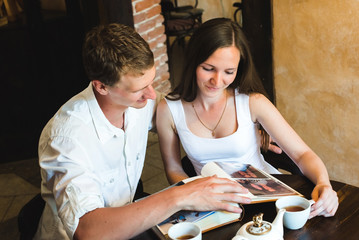 Young couple watching a family photo album. A sweet couple watching their photos from the album in a nice cafe, smiling nostalgically