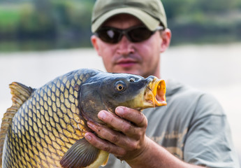 Happy angler with carp fishing trophy