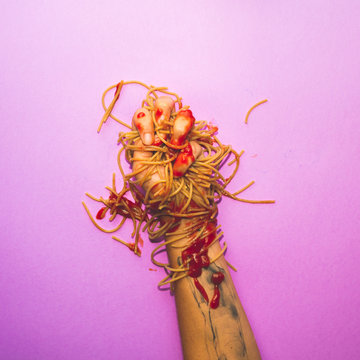 spaghetti mess on hand, trendy colored minimal background