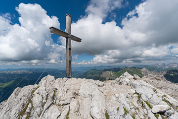Gipfelkreuz vor wolkigem Himmel