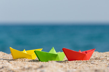 Close up of paper boats in different colors on sandy beach. Ocean in the background. Summer vacation and travel concepts.
