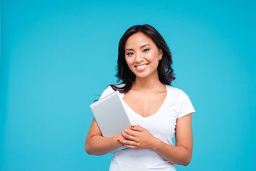Smiling young woman holding tablet computer and looking at camera