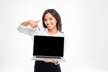 Smiling asian businesswoman pointing at laptop with blank screen