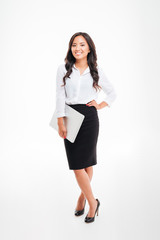 Full length portrait of a smiling asian businesswoman holding laptop