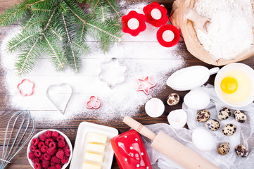 Ingredients for cooking christmas baking. Flour, eggs, butter, raspberries, milk, rolling pin, whisk and cookie cutters on old wooden background. Christmas background. Cooking for festive dinner