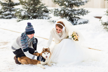 Wedding couple with a dog in winter