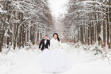 bride and groom is running on a winter park