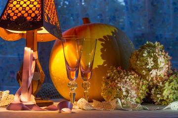Pumpkin, glass cups, hydrangea, fonr and lamp warm light. Romant