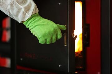 Human hand opening boiler door, closeup