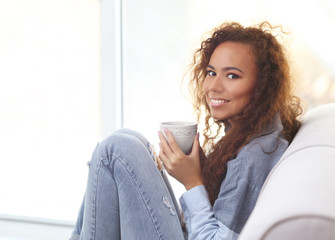 Beautiful African American girl drinking coffee on couch