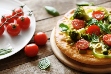 Plate with tasty vegetarian pizza on wooden table