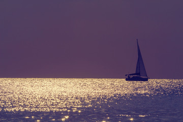 Boat floating on the sea in sunset.