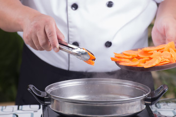 Chef putting carrot for cooking