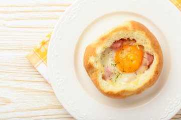 Bun baked with egg, cheese  and ham on white wooden table.