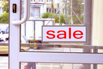 A sign with red letters SALE  on the front door