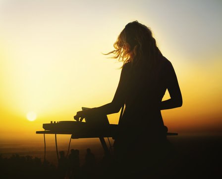 Silhouette of a woman dj at sunset