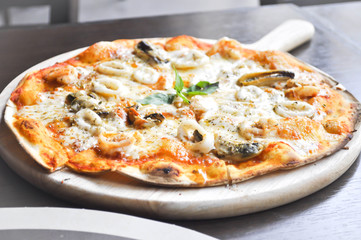 seafood pizza in the wooden  tray or thin pizza