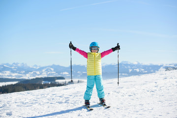 Smiling skier girl has fun on a sunny day in the mountains