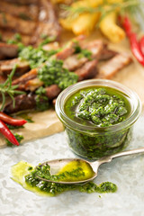 Green chimichurri sauce with grilled steak