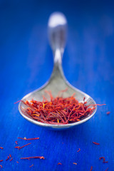Macro of saffron threads in teaspoon on blue background