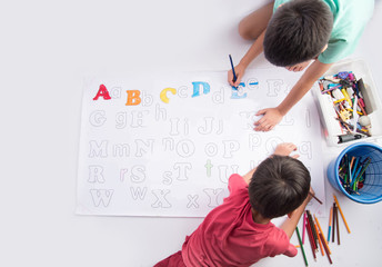 Little child boy painting and coloring alphabet  in the paper indoor activities