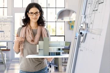 Female architect designer with building model