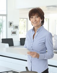 Casual senior businesswoman at home with tablet