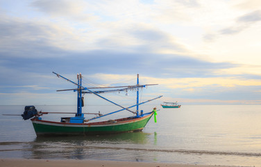 fishing boat floating  in a sand sea with sunrise