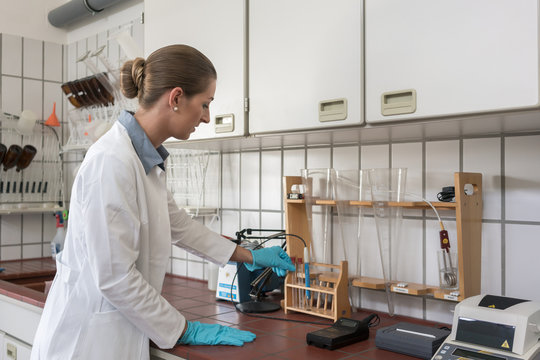 Lab assistant in wastewater treatment plant testing sample for purity