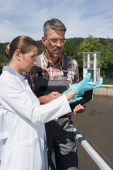 Engineer and laboratory technician in wastewater treatment plant discussing purity of water sample