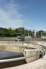 Wastewater treatment plant - man and woman standing at sedimentation tank