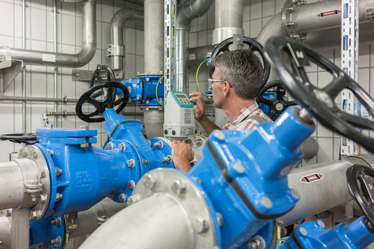 Worker in wastewater treatment plant opening valve in sewage sludge drying pipes