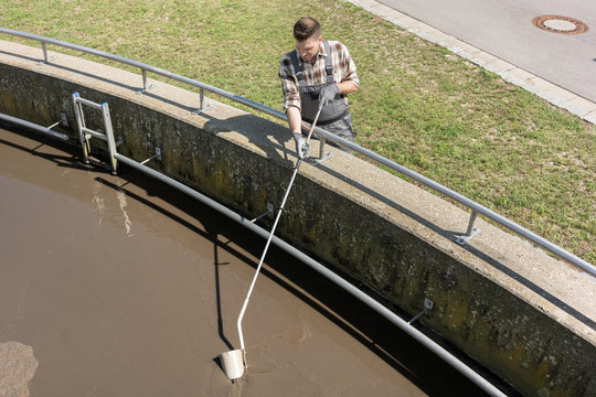 Worker taking water sample out of clarifier tank of sewage treatment plant