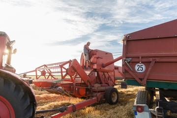 Farmer preparing tractor and combine for harvesting grain field
