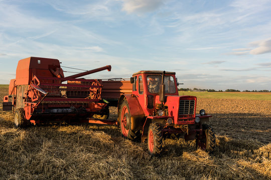 Farmer with his tractor and combine trailer finishing harvest day