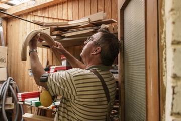 Craftsman in his workshop controlling piece of bentwood, maybe for a window