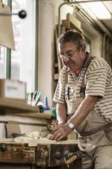 Craftsman in carpentry workshop smoothing wooden workpiece with planer