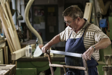 Craftsman in his wood workshop adjusting hacksaw