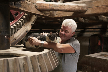 Miller stroking windmill  employee cat for mice control and grain safety