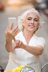 Adult woman touches phone. Lady looking at cell phone. Taking photos during travel. Send a message home.