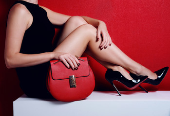woman legs in high heels fashion shoes with red bag