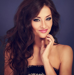 Beautiful makeup woman with long volume hairdo and hand near fac